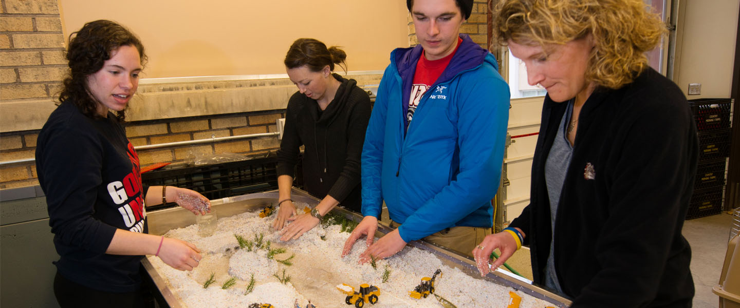 Professor and students work with river simulation