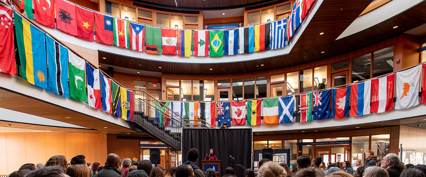 Decorative image, group gathered to hear a speaker. Global country flags hang off balcony.